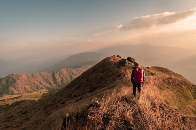Viajero joven con mochila trekking en montaña