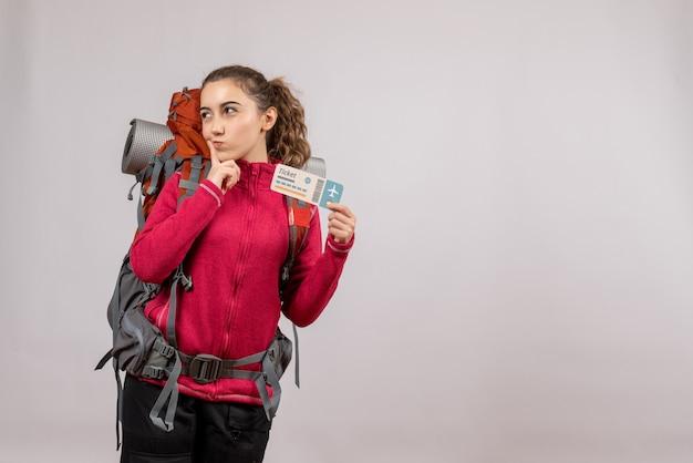 Viajero joven pensativo con mochila grande sosteniendo boleto de viaje en gris