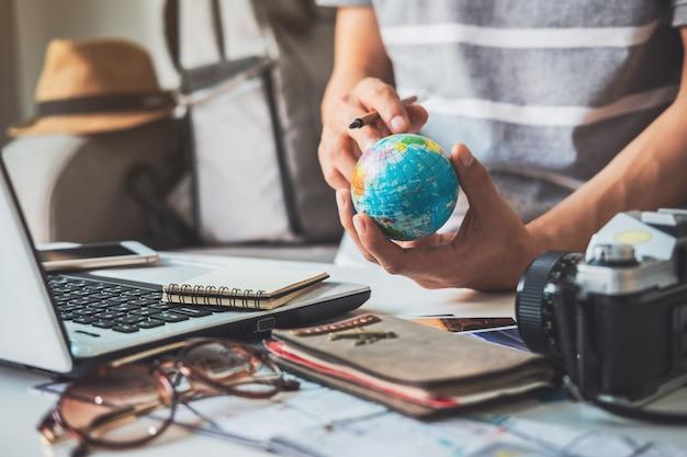 Viajero joven que planea un viaje de vacaciones y busca información o reserva hotel en una computadora portátil, concepto de viaje