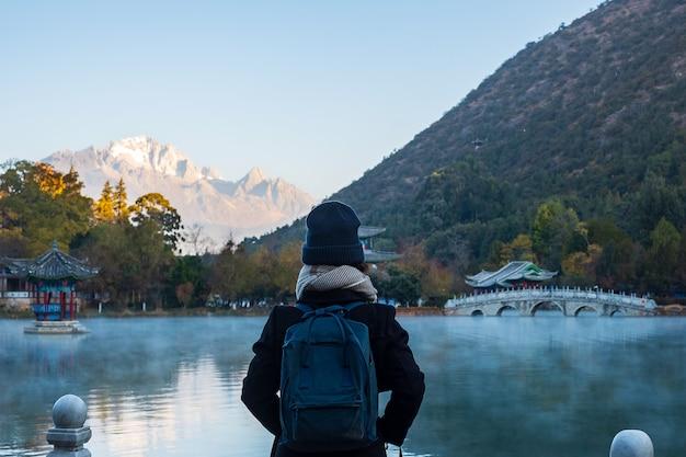 Viajero joven que viaja a black dragon pool con jade dragon snow mountain, punto de referencia y lugar popular para las atracciones turísticas cerca del casco antiguo de lijiang. lijiang, yunnan, china