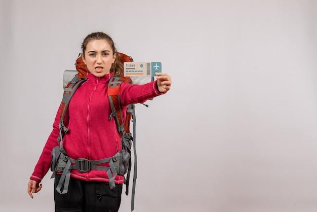 Viajero joven serio con mochila grande sosteniendo billete de viaje en gris