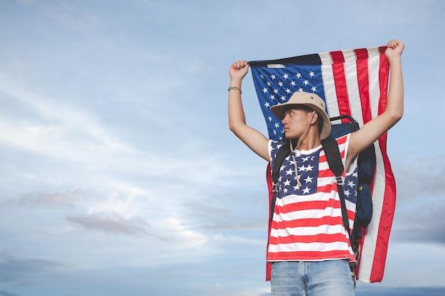 Viajero levanta una bandera frente a la vista del cielo