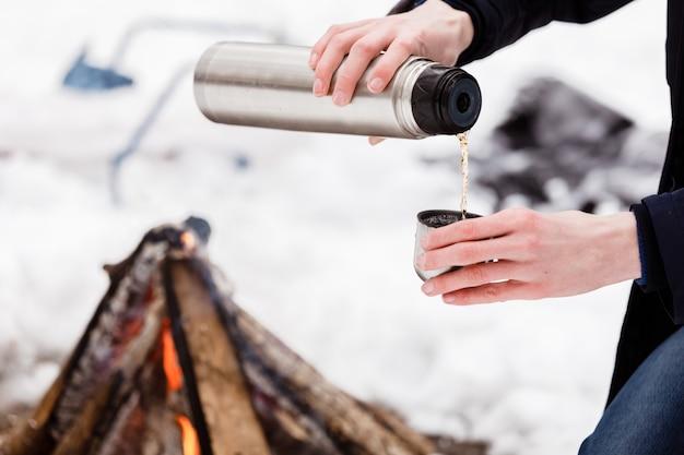 Viajero manos hombre close-up vierte el té de frascos en una taza en el bosque cerca de bonefire.