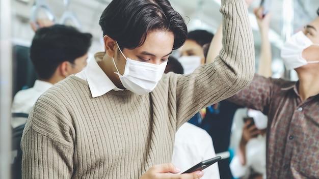 Viajero con máscara facial mientras usa el teléfono móvil en el tren público. enfermedad por coronavirus o brote pandémico de covid 19 y problema de estilo de vida urbano en la ciudad en concepto de desplazamiento en hora punta.