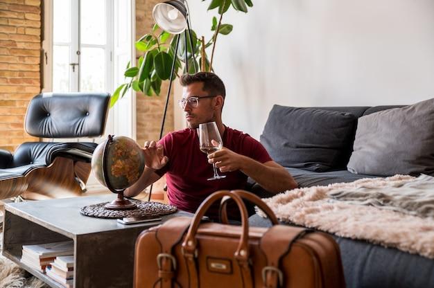 Viajero masculino encantado que elige el país en el planeta tierra antes de la aventura mientras está sentado en la habitación con la maleta