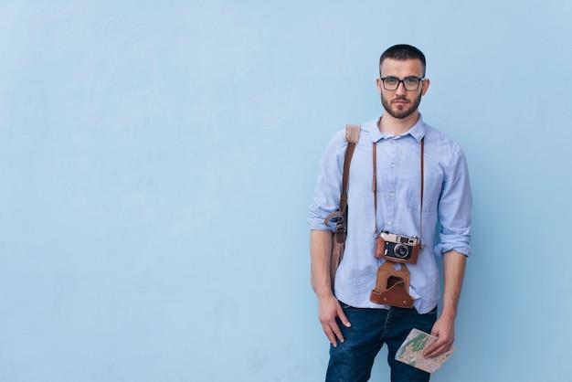 Viajero masculino joven con la cámara alrededor de su cuello que se coloca cerca de fondo azul