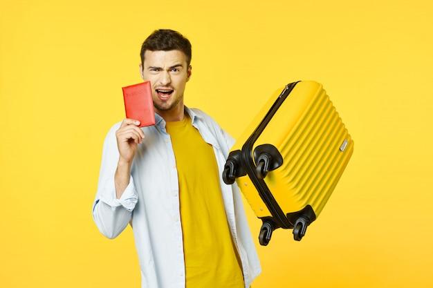 Viajero masculino con una maleta, superficie coloreada, alegría, pasaporte