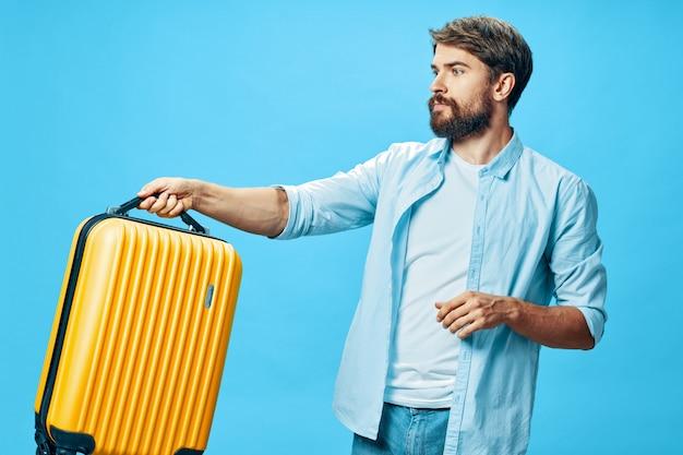 Viajero masculino con una maleta en sus manos posando en estudio, vacaciones