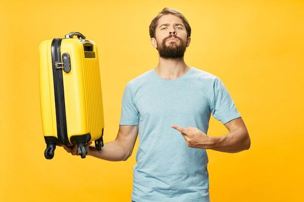 Viajero masculino con una maleta en sus manos posando en studio