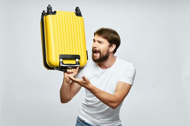 Viajero masculino con una maleta en sus manos posando, vacaciones