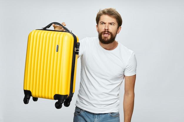 Viajero masculino con una maleta en sus manos posando