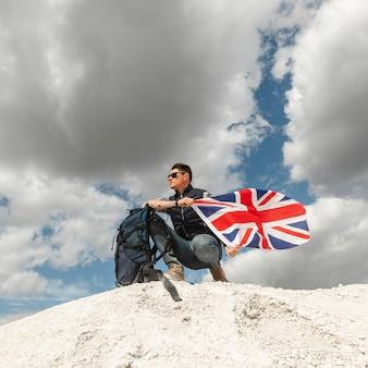 Viajero masculino con mochila y bandera