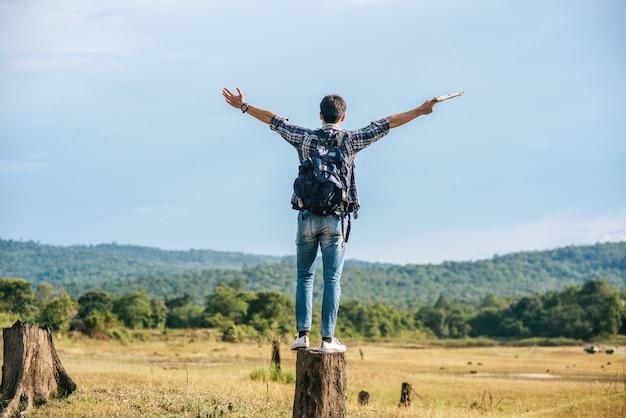 Un viajero masculino con una mochila, llevando un mapa y de pie sobre un tocón de árbol