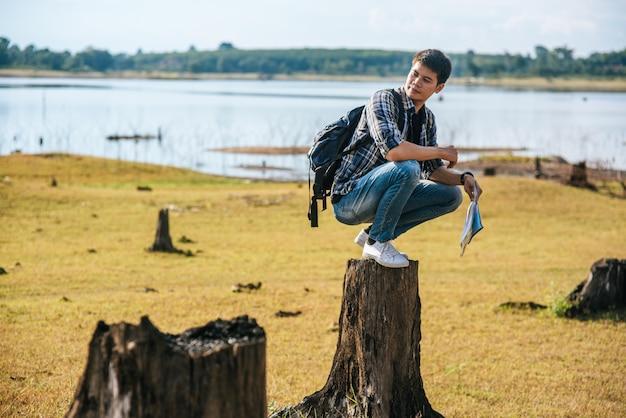 Un viajero masculino con una mochila con un mapa y sentado en un tocón de árbol.