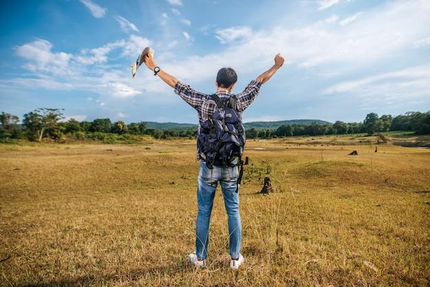 Un viajero masculino con una mochila que lleva un mapa y de pie en el prado.