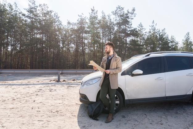 Viajero masculino de pie cerca de su lujoso coche con mapa en la mano mirando lejos