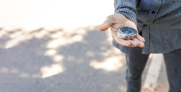 Viajero masculino que sostiene una brújula magnética en la carretera asfaltada, orientación y búsqueda de su camino.
