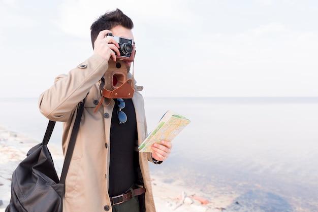 Un viajero masculino que sostiene el mapa en la mano que toma la foto en cámara en la playa