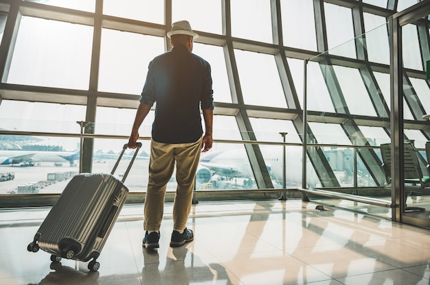 Un viajero masculino con un sombrero gris preparándose para viajar