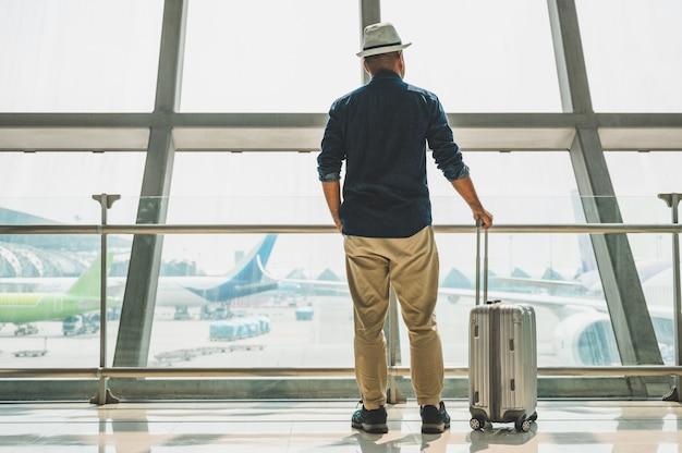 Viajero masculino con un sombrero gris preparándose para viajar