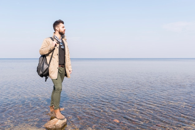 Viajero masculino con su mochila mirando el idílico lago tranquilo