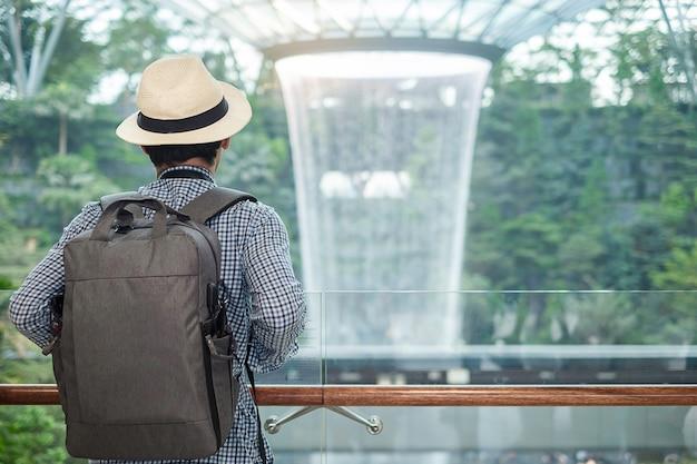 Viajero mirando al hermoso vórtice de lluvia en jewel changi airport