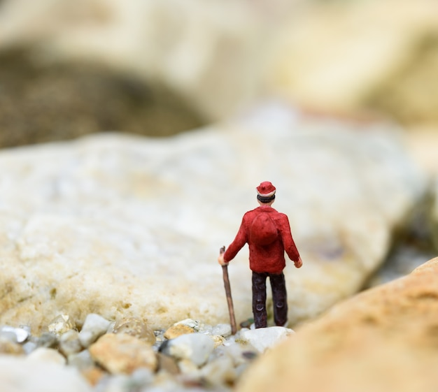 Viajero de mochila en miniatura senderismo roca solo, concepto de viaje
