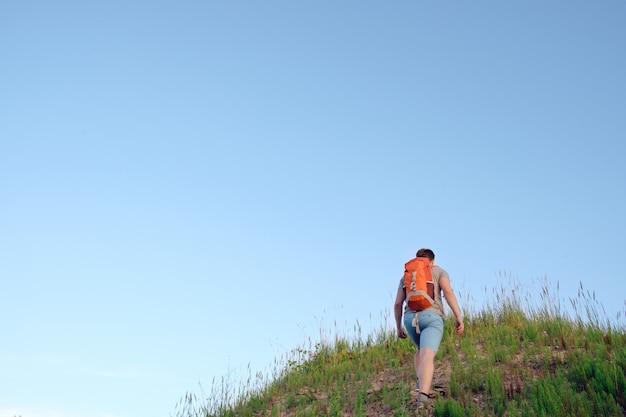 Viajero con mochila naranja senderismo en las colinas en el cielo azul, vista desde atrás