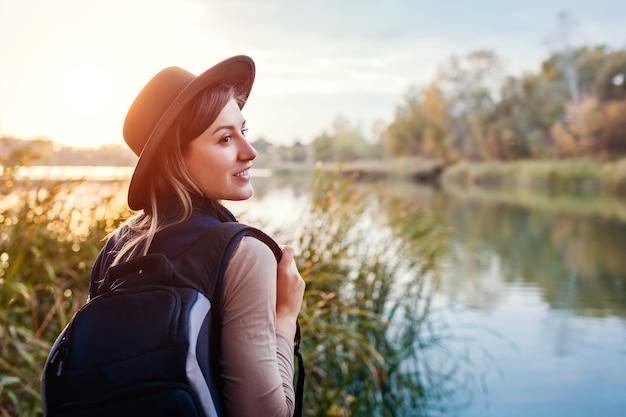 Viajero con mochila relajante junto al río de otoño al atardecer. feliz joven disfruta del clima y el paisaje otoñal. estilo de vida activo
