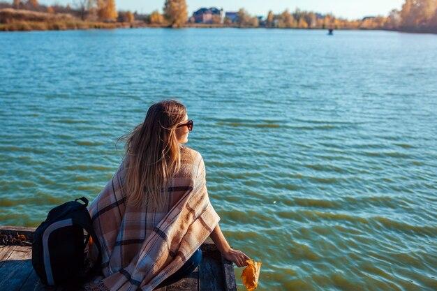 Viajero con mochila relajante junto al río de otoño al atardecer. mujer joven sentada en el muelle admirando el paisaje. estilo de vida activo
