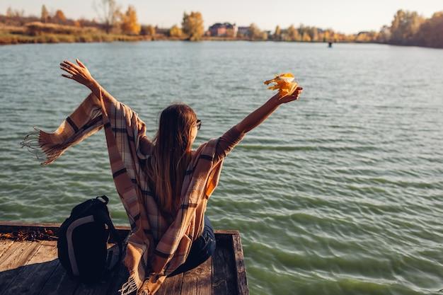 Viajero con mochila relajante por otoño río al atardecer. joven levantó los brazos sintiéndose libre y feliz