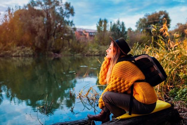 Viajero con mochila relajante por otoño río al atardecer. joven viaja sola