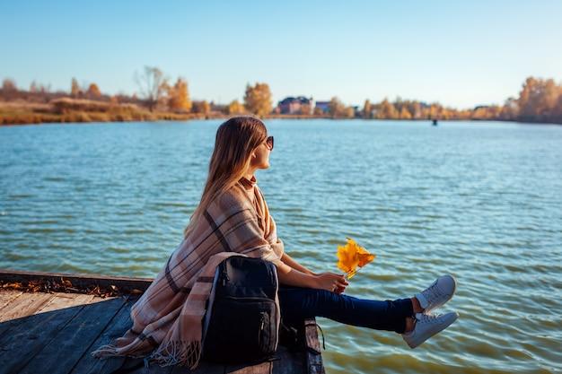 Viajero con mochila relajante por otoño río al atardecer. mujer joven sentada en el muelle admirando el paisaje