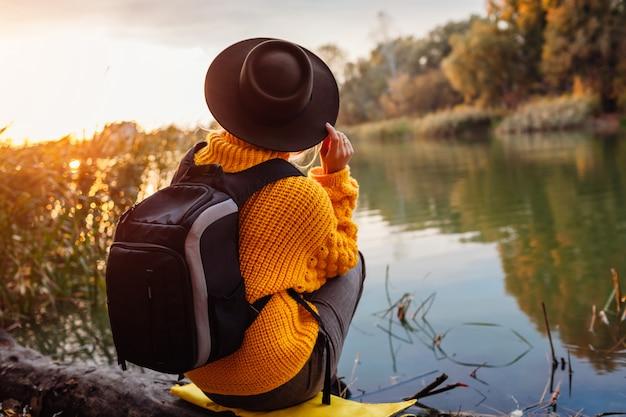 Viajero con mochila relajante en otoño río al atardecer '