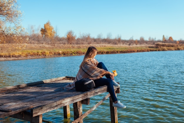 Viajero con mochila relajante por el río de otoño al atardecer con hojas. mujer joven sentada en el muelle admirando el paisaje y el clima. estilo de vida activo
