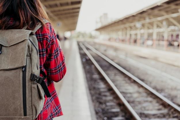 Viajero mochilero joven asiática caminando solo en la plataforma de la estación de tren con mochila