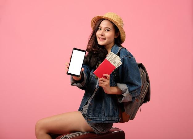 Viajero mochilero mujer con teléfono inteligente, pasaporte y dinero