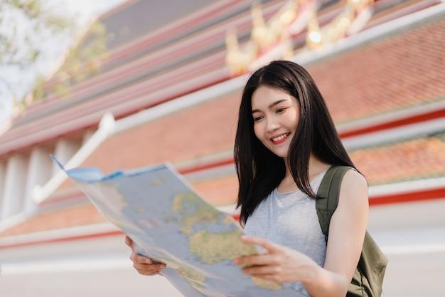 Viajero mujer asiática dirección en mapa de ubicación en bangkok, tailandia