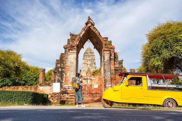 Viajero mujer asiática joven con mochila viajando y tomar una foto en cámara vintage