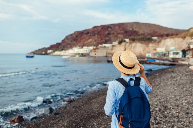 Viajero mujer caminando por la playa de vlychada en akrotiri en la isla de santorini, grecia. turista admirando el paisaje del mar