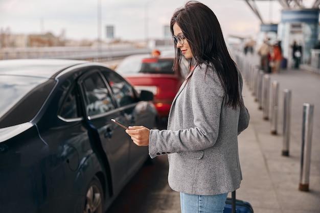 Viajero mujer caucásica feliz en la terminal del aeropuerto está tomando un taxi