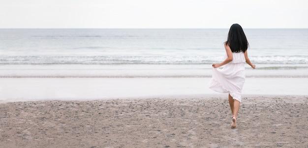 Viajero mujer corre en la playa del mar