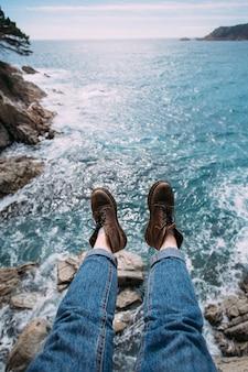 Viajero mujer en jeans azul y botas de cuero marrón grueso para aventuras de senderismo se sienta en el borde del acantilado
