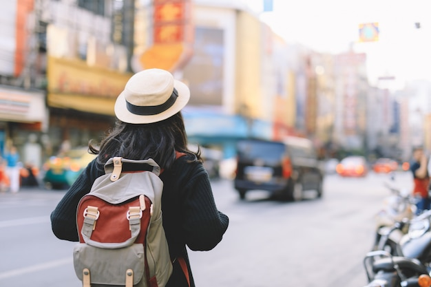 Viajero de la mujer joven con la mochila y el sombrero que mira la calle de china town en bangkok.