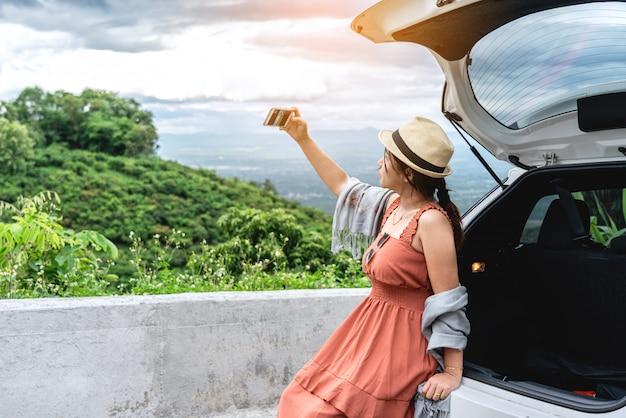 Viajero mujer joven sentada en la parte trasera del coche y tomando selfie foto