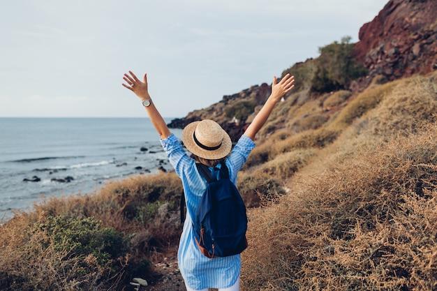 El viajero de la mujer levantó los brazos sintiéndose feliz en la playa de akrotiri, isla de santorini, grecia en otoño. turismo, viajar