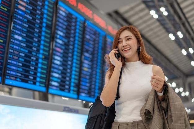Viajero de la mujer en llamada del teléfono móvil en el tablero de la información del vuelo en aeropuerto