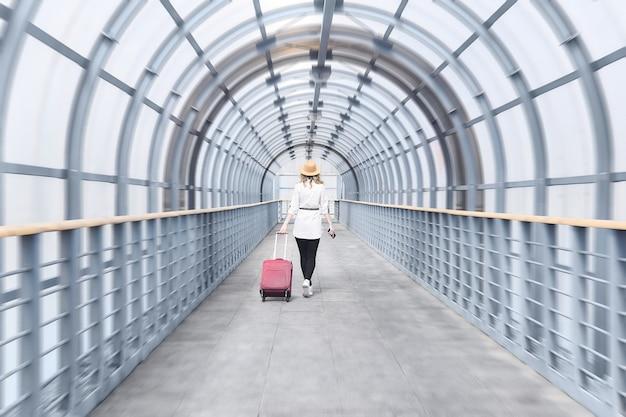 Viajero mujer con una maleta se adentra en la distancia a lo largo de la galería del pasaje cubierto