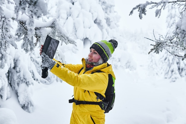 Viajero de mujer con una mochila en un bosque nevado de invierno graba video con ella misma por teléfono inteligente