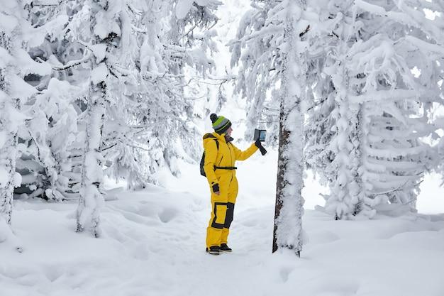 Viajero de mujer con una mochila en un bosque nevado de invierno graba video por teléfono inteligente